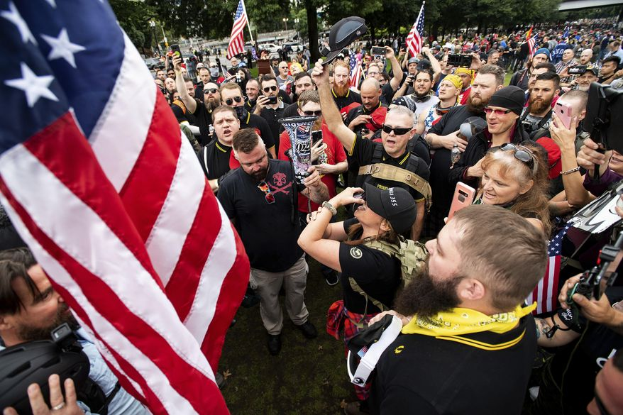 FILE - In this Aug. 17, 2019, file photo, members of the Proud Boys and other right-wing demonstrators plant a flag in Tom McCall Waterfront Park during a rally in Portland, Ore. At least several thousand people are expected in Portland on Saturday, Sept. 26, 2020, for a rally in support of President Donald Trump and his re-election campaign as tensions boil over nationwide following the decision not to charge officers in Louisville, Kentucky for killing Breonna Taylor. (AP Photo/Noah Berger, File)