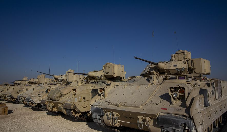 """In this Nov. 11, 2019, file photo, Bradley Fighting Vehicles are parked at a U.S. military base at an undisclosed location in Northeastern Syria, Monday, Nov. 11, 2019. On Dec. 18, 2020, the Pentagon released its final request for proposals for an """"optionally manned fighting vehicle"""" to be the next-generation platform to replace the Bradley Fighting Vehicle. (AP Photo/Darko Bandic, File)  **FILE**"""