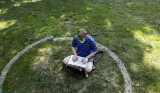 FILE - In this Aug. 25, 2020, file photo, Logan Armstrong, a junior, works while sitting inside a painted circle on the lawn of the Oval during the first day of fall classes at Ohio State University in Columbus, Ohio.   Colleges across the country are struggling to salvage the fall semester as campus coronavirus cases skyrocket and tensions with local health leaders flare. Schools have locked down dorms, imposed mask mandates, barred student fans from football games and toggled between online and in-person classes.   (Joshua A. Bickel/The Columbus Dispatch via AP, File)