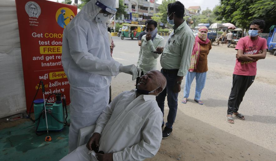 A health worker takes a nasal swab sample to test for COVID-19 test in Ahmedabad, India, Saturday, Sept. 26, 2020. The nation of 1.3 billion people is expected to become the pandemic's worst-hit country within weeks, surpassing the United States. (AP Photo/Ajit Solanki)