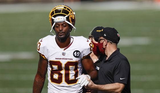 Washington Football Team wide receiver Dontrelle Inman (80) walks off the field with a trainer after being injured against the Cleveland Browns during the second half of an NFL football game, Sunday, Sept. 27, 2020, in Cleveland. (AP Photo/Ron Schwane)