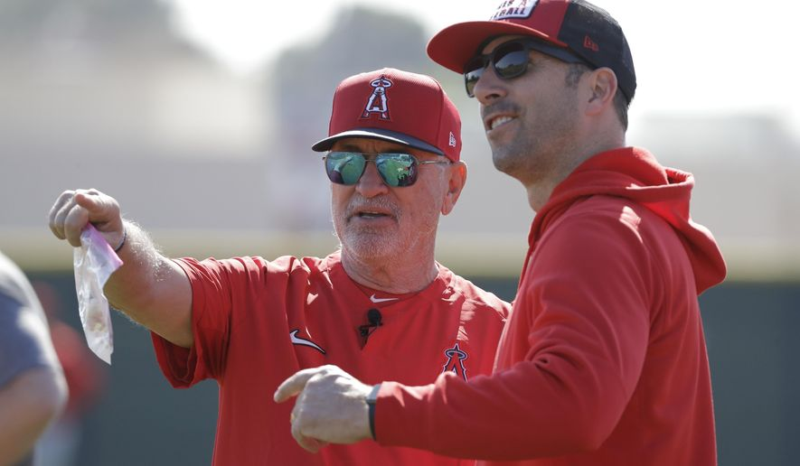 Los Angeles Angels manager Joe Maddon talks with general manager Billy Eppler during spring training baseball practice, Monday, Feb. 17, 2020, in Tempe, Ariz. (AP Photo/Darron Cummings)