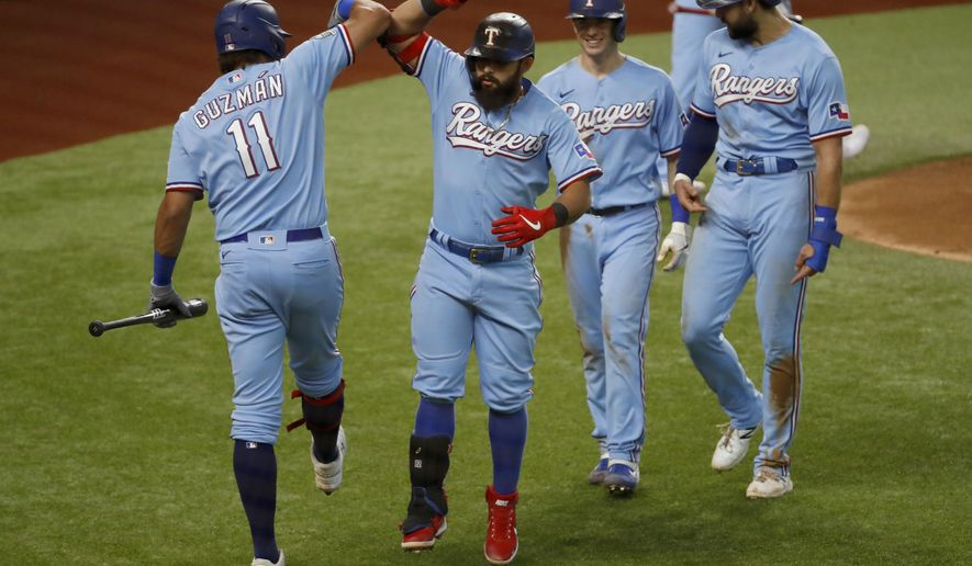 Texas Rangers' Ronald Guzman (11) congratulates Rougned Odor, second from left, for hitting a three-run home run while Nick Solak, second from right, and Joey Gallo, right, look on during the fourth inning of a baseball game against the Houston Astros in Arlington, Texas, Sunday, Sept. 27, 2020. (AP Photo/Roger Steinman)