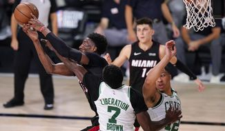 Miami Heat's Bam Adebayo, left, battles for a rebound along with Boston Celtics' Jaylen Brown (7) and teammate Grant Williams (12) during the second half of an NBA conference final playoff basketball game Sunday, Sept. 27, 2020, in Lake Buena Vista, Fla. (AP Photo/Mark J. Terrill)