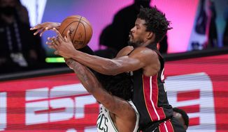 Miami Heat's Jimmy Butler, right, goes over the top of Boston Celtics' Marcus Smart (36) during the second half of an NBA conference final playoff basketball game Sunday, Sept. 27, 2020, in Lake Buena Vista, Fla. (AP Photo/Mark J. Terrill)  **FILE**