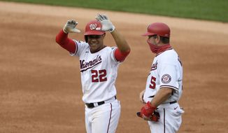 Washington Nationals' Juan Soto (22) reacts at first after his single during the second inning of a baseball game against the New York Mets, Sunday, Sept. 27, 2020, in Washington. Nationals first base coach Bob Henley, right. (AP Photo/Nick Wass)