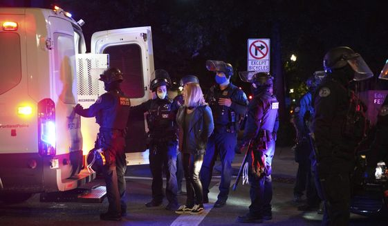 In this file photo, a female protester is loaded into a van after being arrested while rallying at the Mark O. Hatfield United States Courthouse on Saturday, Sept. 26, 2020, in Portland, Ore. A Harvard poll released Oct. 1 suggests Americans are open to President Trump's law-and-order campaign message. (AP Photo/Allison Dinner)
