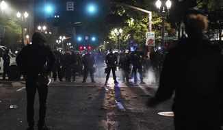 Portland Police line up blocking the street while protesters rally in front of them at the Mark O. Hatfield United States Courthouse on Saturday, Sept. 26, 2020, in Portland, Ore. (AP Photo/Allison Dinner)