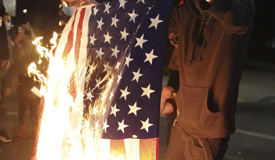 A protester burns an American flag while rallying at the Mark O. Hatfield United States Courthouse on Saturday, Sept. 26, 2020, in Portland, Ore. The rally came as Portland has seen nearly nightly protests since the police killing of George Floyd in late May. (AP Photo/Allison Dinner)