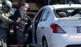 An unidentified woman is taken into custody after witnesses said she drove her car into a crowd of protesters in Yorba Linda, Calif., Saturday, Sept. 26, 2020. Authorities said people were struck by a car and injured during a Black Lives Matter protest and counter protest about 30 miles southeast of Los Angeles. Orange County Sheriff's Department spokeswoman Carrie Braun says the injured were transported to a hospital with non-life-threatening injuries and the driver was detained. (Mindy Schauer/The Orange County Register via AP)