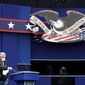 A worker sprays sanitizer on a lectern as preparations take place for the first presidential debate in Cleveland. (Associated Press)