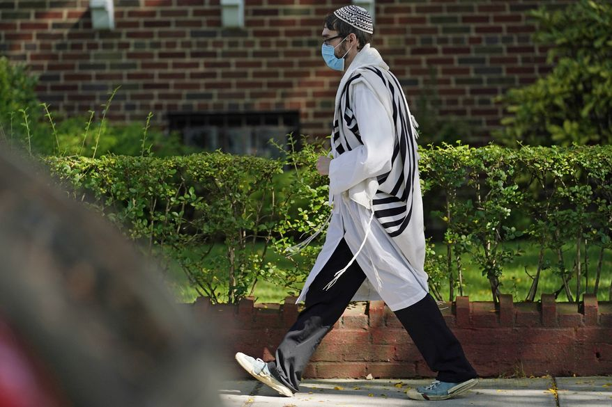 An Orthodox Jewish man wearing traditional garb required on the Jewish high holiday of Yom Kippur walks through the Midwood neighborhood of Brooklyn, Monday, Sept. 28, 2020, in New York. New York Gov. Andrew Cuomo raised an alarm Monday about the emergence of a handful of coronavirus hot spots in New York, saying just 10 ZIP codes represented more than a quarter of the state's new infections in recent testing. Midwood, home to a large Orthodox Jewish population, is one of the neighborhoods experiencing an uptick in COVID-19 cases. (AP Photo/Kathy Willens)