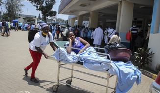 A patient is wheeled out of the Accident and Emergency ward after medical workers downed tools over poor pay and allowances at Kenya's largest referral hospital Kenyatta National Hospital in Nairobi, Kenya Monday, Sept. 28, 2020. A witness says a man has died outside an emergency ward of Kenya's largest referral hospital after he was not treated for hours because the staff are on strike over pay raises that were approved in 2012 but according to medical workers not received. (AP Photo)