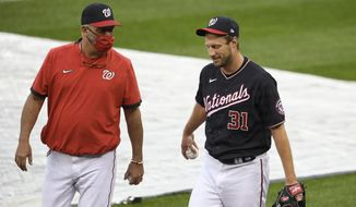 Washington Nationals starting pitcher Max Scherzer (31) walks on the field next to pitching coach Paul Menhart, left, before a baseball game against the New York Mets, Friday, Sept. 25, 2020, in Washington. The game was postponed due to inclement weather. (AP Photo/Nick Wass)  **FILE**