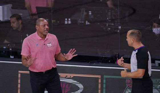 Los Angeles Clippers head coach Doc Rivers, left, questions a call during the first half of an NBA conference semifinal playoff basketball game against the Denver Nuggets, Tuesday, Sept. 15, 2020, in Lake Buena Vista, Fla. (AP Photo/Mark J. Terrill)  **FILE**