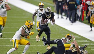 New Orleans Saints running back Alvin Kamara (41) leaps as he carries on a 52 yard touchdown pass play in the second half of an NFL football game against the Green Bay Packers in New Orleans, Sunday, Sept. 27, 2020. (AP Photo/Brett Duke)