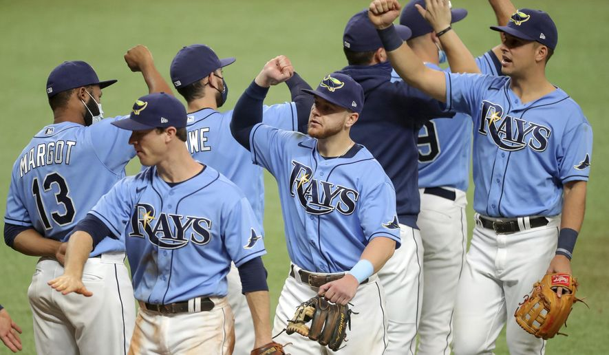 Members of the Tampa Bay Rays celebrate a 5-0 win over the Philadelphia Phillies in a baseball game Sunday, Sept. 27, 2020, in St. Petersburg, Fla. (AP Photo/Mike Carlson)
