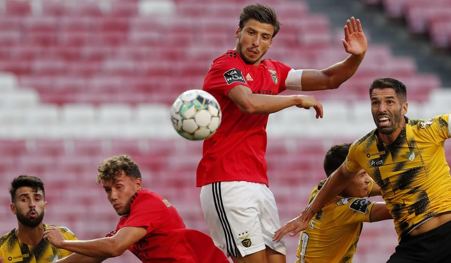 Benfica's Ruben Dias, center, heads the ball to score the opening goal during the Portuguese League soccer match between Benfica and Moreirense at the Luz stadium in Lisbon, Saturday, Sept. 26, 2020. (AP Photo/Armando Franca)