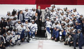 Tampa Bay Lightning players surround NHL Commissioner Gary Bettman as they celebrate after defeating the Dallas Stars to win the Stanley Cup in Edmonton, Alberta, on Monday, Sept. 28, 2020. (Jason Franson/The Canadian Press via AP)