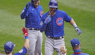 Chicago Cubs' Kris Bryant, top right, is congratulated by teammates after hitting a solo home run during the second inning of a baseball game against the Chicago White Sox in Chicago, Sunday, Sept. 27, 2020. (AP Photo/Nam Y. Huh)