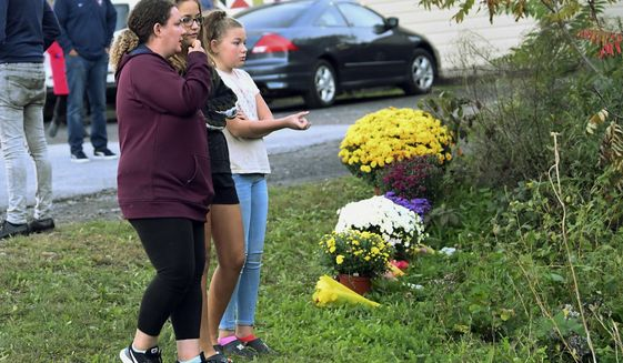FILE - In this Oct. 7, 2018 file photo, friends of victims that died in a fatal limousine crash comfort each other after placing flowers at the intersection of the accident in Schoharie, N.Y. Federal investigators examining the 2018 crash of a stretch limousine that killed 20 people said Tuesday, Sept. 29, 2020, that state regulators repeatedly failed to oversee a poorly maintained vehicle with corroded brakes.  (AP Photo/Hans Pennink, File)