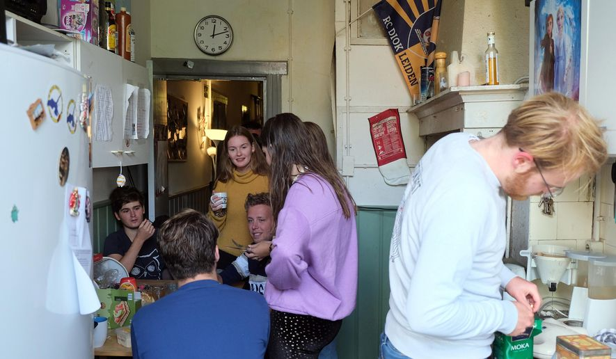 Dutch students chat in the kitchen of their shared house in Leiden, Netherlands on Friday, Sept. 25, 2020. The coronavirus pandemic is hitting students hard in Leiden, the Netherlands' oldest university city. With the coronavirus casting a long shadow over education here and around the world, most lectures are online, and the vibrant social life has been reined in to slow the spread of the pandemic. (AP Photo/Mike Corder)