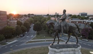 In this July 31, 2017, file photo, the sun sets behind the statue of Confederate Gen. Robert E. Lee on Monument Avenue in Richmond, Va. (AP Photo/Steve Helber, File)  **FILE**