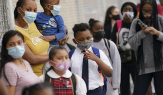 FILE - In this Sept. 9, 2020, file photo, students wear protective masks due to COVID-19 as they arrive for classes at the Immaculate Conception in The Bronx borough of New York. After being delayed twice, hundreds of thousands of elementary public school students are heading back to classrooms Tuesday, Sept. 29 as New York City enters a high-stakes phase of resuming in-person learning during the coronavirus pandemic. (AP Photo/John Minchillo, File)