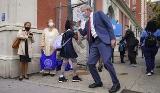New York Mayor Bill de Blasio, center right, greets students as they arrive for in-person classes outside Public School 188 The Island School, Tuesday, Sept. 29, 2020, in the Manhattan borough of New York. Hundreds of thousands of elementary school students are heading back to classrooms starting Tuesday as New York City enters a high-stakes phase of resuming in-person learning during the coronavirus pandemic. (AP Photo/John Minchillo)