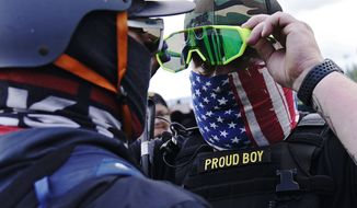"A member of the Proud Boys, right, stands in front of a counter protester as members of the Proud Boys and other right-wing demonstrators rally on Saturday, Sept. 26, 2020, in Portland. President Donald Trump didn't condemn white supremacist groups and their role in violence in some American cities this summer. Instead, he said the violence is a left-wing"" problem and he told one far-right extremist group to stand back and stand by. His comments Tuesday night were in response to debate moderator Chris Wallace asking if he would condemn white supremacists and militia groups. Trump's exchange with Democrat Joe Biden left the extremist group Proud Boys celebrating what some of its members saw as tacit approval. (AP Photo/John Locher)"