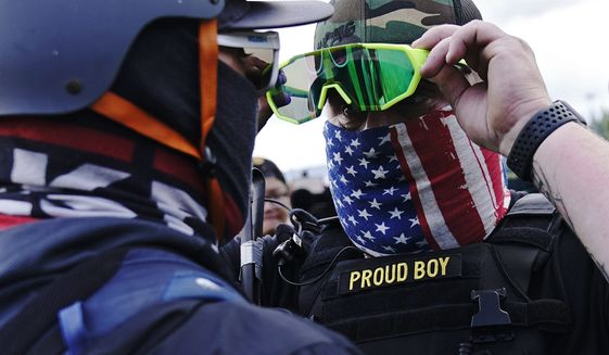 """A member of the Proud Boys, right, stands in front of a counter protester as members of the Proud Boys and other right-wing demonstrators rally on Saturday, Sept. 26, 2020, in Portland. President Donald Trump didn't condemn white supremacist groups and their role in violence in some American cities this summer. Instead, he said the violence is a left-wing"""" problem and he told one far-right extremist group to stand back and stand by. His comments Tuesday night were in response to debate moderator Chris Wallace asking if he would condemn white supremacists and militia groups. Trump's exchange with Democrat Joe Biden left the extremist group Proud Boys celebrating what some of its members saw as tacit approval. (AP Photo/John Locher)"""