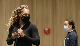 Serena Williams of the U.S., left, leaves after a press conference in which she announced her withdrawal from the tournament because of an Achilles injury prior to her second round match of the French Open tennis tournament at the Roland Garros stadium in Paris, France, Wednesday, Sept. 30, 2020. (AP Photo/Christophe Ena)