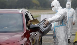 An election committee member, wearing a protective suit, holds a ballot box for a man to vote in regional and senate elections at a drive-in polling station in Prague, Czech Republic, Wednesday, Sept. 30, 2020. Czechs are casting ballots from their cars for the first time, a measure forced by the coronavirus pandemic. A total of 156 drive-in temporary ballot stations have been established by the armed forces across the country for those quarantined due to COVID-19. (AP Photo/Petr David Josek)