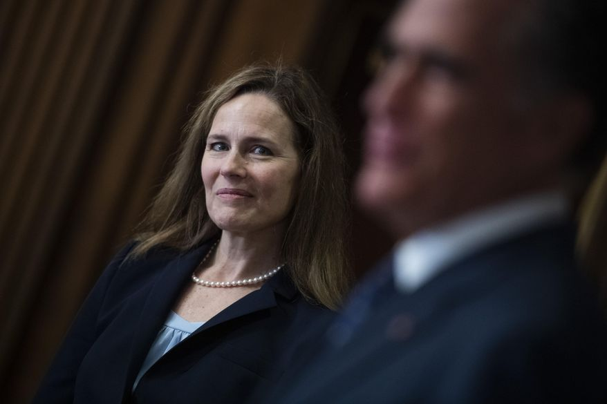 Judge Amy Coney Barrett, President Donald Trumps nominee for the U.S. Supreme Court, meets with Sen. Mitt Romney, R-Utah, on Capitol Hill in Washington, Wednesday, Sept. 30, 2020. (Tom Williams/Pool via AP)
