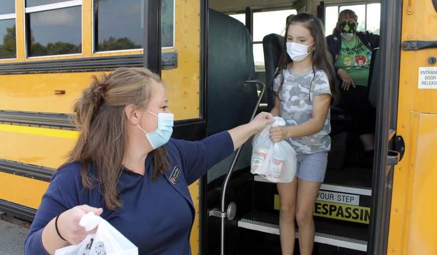 Jessica O'Brien, left, development director at the Salvation Army of Michigan City, and Kennedy Baker pack groceries into a bus at Al's Supermarket on Franklin Street on Saturday, Sept. 26, 2020, in Michigan City, Ind. It was the organization's annual Stuff A Bus initiative to gather food donations for families in need of holiday assistance. (Kelley Smith/The News Dispatch via AP)