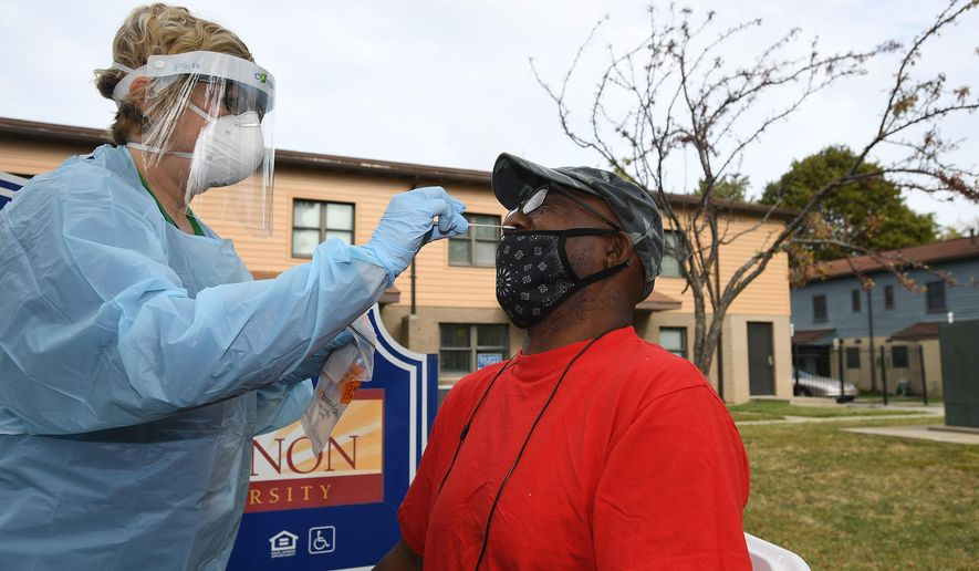 Toni Gomacki, L.P.N., 51, left, performs a COVID-19 test on Curtis Morrow, 60, of Erie, outside the John Horan Apartments on Sept. 29, 2020, in Erie, Pa. The free coronavirus tests were provided by Latino Connection, a Harrisburg-based Latino and minority outreach company. The mobile unit, called CATE, for community-accessible testing and education, provided 100 tests in Erie, and another 100 were available later in the day in Corry, Pa. (Christopher Millette/Erie Times-News via AP)