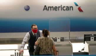 American Airlines ticket agent Henry Gemdron, left, works with a customer at Miami International Airport during the coronavirus pandemic, Wednesday, Sept. 30, 2020, in Miami. (AP Photo/Lynne Sladky, File)