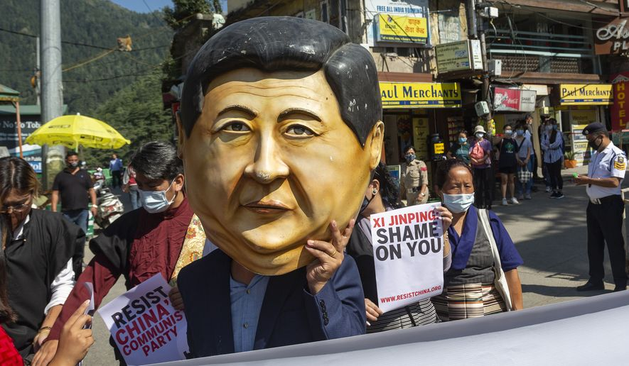 An exile Tibetan representing Chinese President Xi Jinping marches with others during a street protest in Dharmsala, India, Thursday, Oct. 1, 2020. Various Tibetan organizations marked China's National Day by highlighting the country's human rights record. (AP Photo/Ashwini Bhatia)