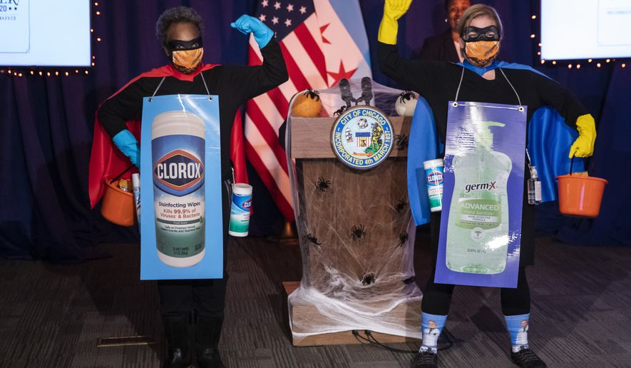 """Chicago Mayor Lori Lightfoot, left,  and Dr. Allison Arwady, commissioner of the Chicago Department of Public Health, wear """"Rona Destroyer"""" costumes as they pose a press conference about Halloween at City Hall, Thursday afternoon, Oct. 1, 2020, in Chicago. City officials say Chicagoans going door-to-door on Halloween this year will have to wear masks and keep groups small to minimize risks of the coronavirus. (Ashlee Rezin Garcia/Chicago Sun-Times via AP)"""