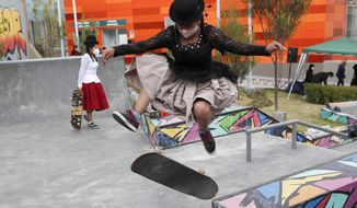 "Aide Choque, wearing a mask amid the COVID-19 pandemic, jumps with her skateboard during a youth talent show in La Paz, Bolivia, Wednesday, Sept. 30, 2020. Young women called ""Skates Imillas,"" using the Aymara word for girl Imilla, use traditional Indigenous clothing as a statement of pride of their Indigenous culture when riding their skateboards. (AP Photo/Juan Karita)"