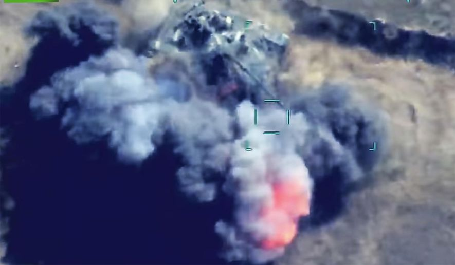 In this photo taken from a video released by the Azerbaijan's Defense Ministry on Wednesday, Sept. 30, 2020, Azerbaijan's forces attack Armenian army's tank during fighting in the self-proclaimed Republic of Nagorno-Karabakh, Azerbaijan. Heavy fighting between Armenian and Azerbaijani has continued for a fourth straight day as statements from both sides indicating that the flare-up of a decades-old conflict that has killed dozens of people this week was no closer to an end. (Azerbaijan's Defense Ministry via AP)