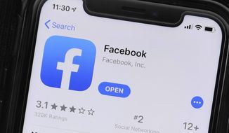 FILE - This July 30, 2019 file photo shows an update information of Facebook application on a mobile phone displayed at a store in Chicago.   Facebook, Wednesday, Sept. 30, 2020, says it's banning any ads that seek to question the validity of an election, including those claiming widespread voter fraud, in its latest move to crack down ahead of the U.S. presidential election.   (AP Photo/Amr Alfiky, File)