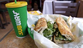In this Friday, Feb. 23, 2018 file photo, the Subway logo is seen on a soft drink cup next to a sandwich at a restaurant in Londonderry, N.H.. Ireland's Supreme Court has ruled that bread sold by the fast food chain Subway contains so much sugar that it cannot be legally defined as bread. (AP Photo/Charles Krupa, File)