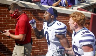 Kansas State linebacker Elijah Sullivan (0) and defensive back Hunter Henry (36) yell while going to their locker room after a win over Oklahoma in an NCAA college football game in Norman, Okla., Saturday, Sept. 26, 2020. (Ian Maule/Tulsa World via AP)