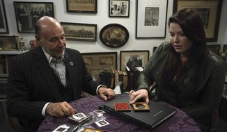 """This image released by Discovery shows Dr. Stanley Burns, left, and Dr. Whitny Braun looking over a photo of what some believe is Abraham Lincoln, captured hours after his death on April 15, 1865, in a scene from the documentary """"The Lost Lincoln."""" After looking into it for two years, Braun said she's 99 percent convinced the photo is genuine. The documentary airs on Sunday. (Unrealistic Ideas/Discovery via AP)"""