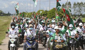 Supporters of the. military-backed Union Solidarity and Development Party (USDP) wave the party flags and cheer from their motorbikes during an election campaign for next month's  general election, Thursday, Oct. 1, 2020, in Naypyitaw, Myanmar. (AP Photo/Aung Shine Oo)
