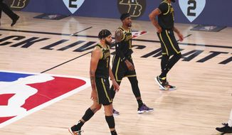 """FILE - In this Aug. 24, 2020, file photo, Los Angeles Lakers center JaVale McGee (7), guard Kentavious Caldwell-Pope (1) and forward Anthony Davis (3) walk in front of the boards remembering late Los Angeles Lakers player Kobe Bryant in the first half of Game 4 of an NBA basketball first-round playoff series against the Portland Trail Blazers in Lake Buena Vista, Fla. The jerseys will be hanging in their lockers when the Los Angeles Lakers arrive for Game 2 of the NBA Finals on Friday night, Oct. 2. Black jerseys, trimmed in gold, a snakeskin print on the exterior to make it further unique.T hey are the Black Mamba jerseys. Designed by Kobe Bryant — and now worn for Kobe Bryant. """"We never want to lose in these jerseys,"""" Lakers forward Anthony Davis said.(Kim Klement/Pool Photo via AP, File)"""