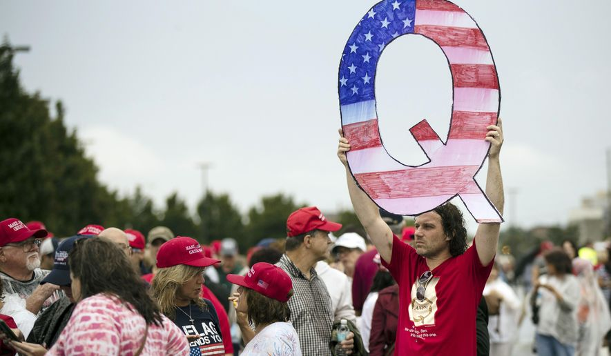In this Aug. 2, 2018, file photo, a protesters holds a Q sign waits in line with others to enter a campaign rally with President Donald Trump in Wilkes-Barre, Pa. (AP Photo/Matt Rourke, File)