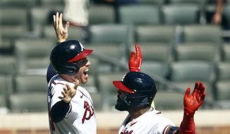Atlanta Braves' Marcell Ozuna, right, and Freddie Freeman celebrate after Ozuna hit a two-run home run in the eighth inning against the Cincinnati Reds in Game 2 of a National League wild-card baseball series, Thursday, Oct. 1, 2020, in Atlanta. (Curtis Compton/Atlanta Journal-Constitution via AP)  **FILE**
