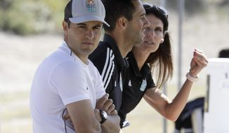 FILE - In this March 4, 2020, file photo San Diego Loyal coach Landon Donovan, left, sits next to assistant coaches Nate Miller, center, and Carrie Taylor during a scrimmage in Chula Vista, Calif. Just before halftime Wednesday, Sept. 30, 2020, and with San Diego leading 3-1, Donovan's expansion Loyal walked off the field and forfeited their USL second division match after openly gay midfielder Collin Martin allegedly was called a homophobic slur by a Phoenix player. (AP Photo/Gregory Bull, File)